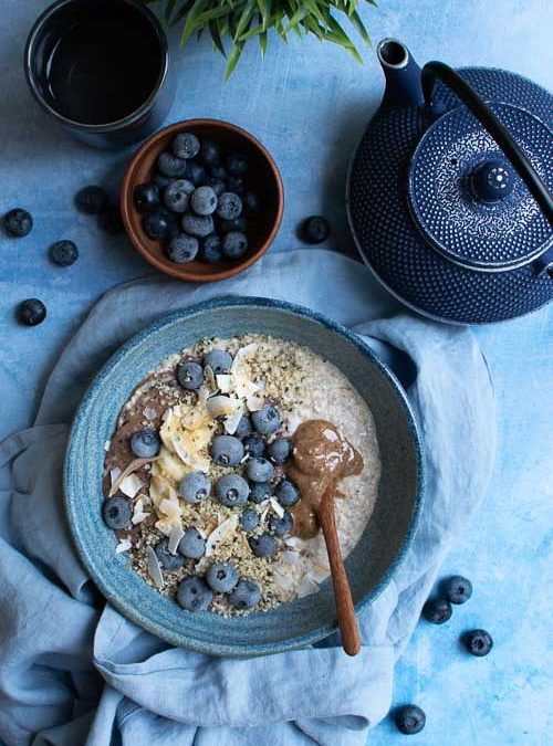 oats blended with banana and coconut milk topped with blueberries, hemp seeds and almond butter