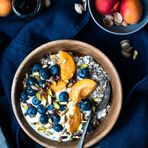 oats and chia porridge with apricot, blueberries, raw caco nibs, pistachios and maple syrup
